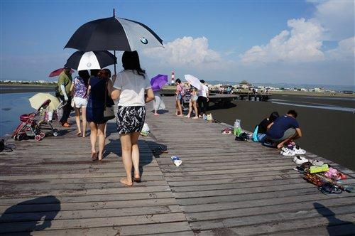 高美濕地的木棧道延伸在灘地上,遊客眾多。